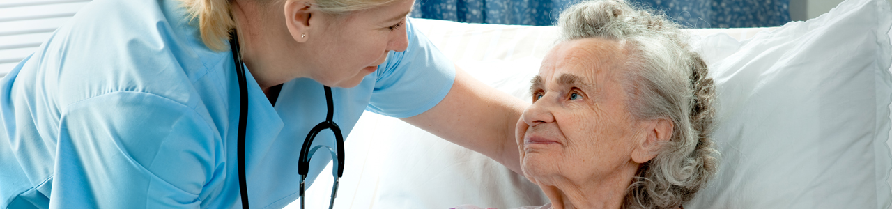 Nurse cares for a elderly patient lying in bed in hospital.
